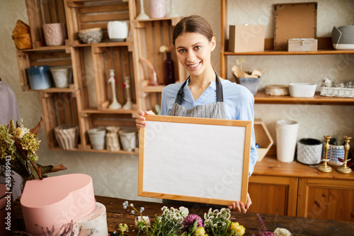 Leinwand Poster Waist up portrait of young female florist holding whiteboard and  looking at cam