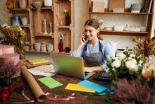 Portrait Of Female Small Business Owner Using Laptop And Speaking By Phone In Flower Shop, Copy Space