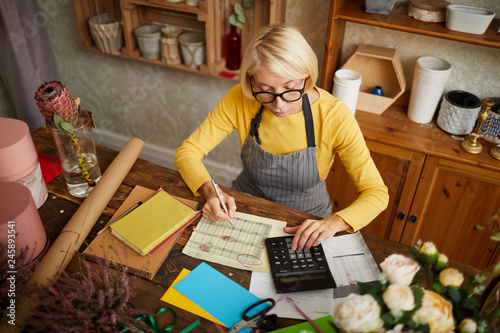 Valokuva High angle portrait of female businesswoman counting finances using calculator i