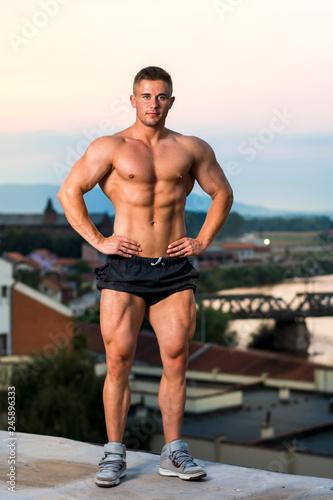 Fotografie, Obraz  Bodybuilder flexing muscles on a rooftop