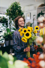 Man Carrying Bouquet Of Sunflowers