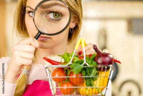 Fotomural Woman investigating shopping backet with vegetables