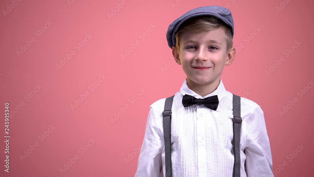 Fototapety, obrazy: Funny little boy in vintage clothes smiling on camera against pink background