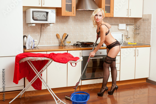 Fotografie, Obraz  Woman in underwear washes the floors in the kitchen.