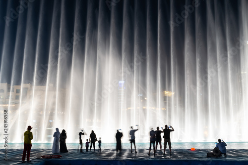 Photo Silhouettes of people enjoying the fountain show in Dubai at night, United Arab