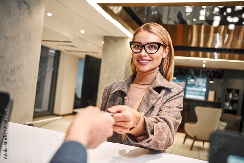 Young woman in hotel check in at reception or front office being given key card Canvas Print