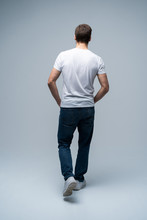 Back View Of A Casual Young Man Walking And Looking To Side On Gray Background.