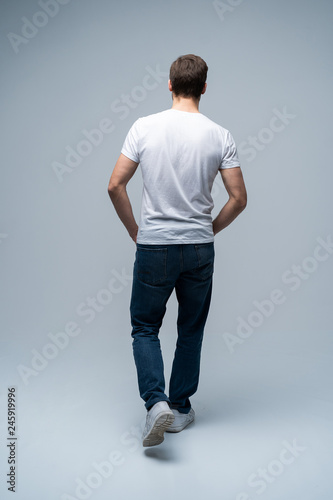 Obraz back view of a casual young man walking and looking to side on gray background. - fototapety do salonu
