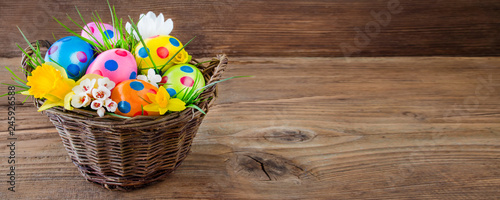 Easter eggs in basket and wooden background