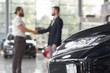 Men shaking hands in modern auto showroom.