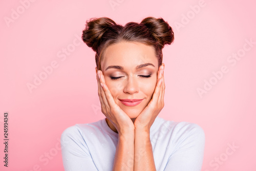 Close-up portrait of her she nice cute lovely attractive fascinating lovable winsome calm girl with buns touching cheeks closed eyes isolated over pink pastel background
