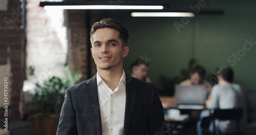 Fotografía  Portrait of young successful businessman at busy office