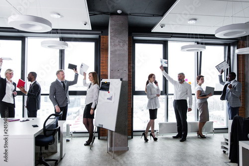 Eight business people stand on the background of a window in