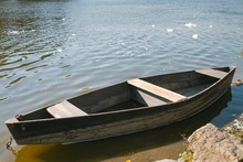 Small Old Wooden Fishing Boat (punt) On The Bank Of A River, Bright Sunny Day, Little Waves On Water Surface