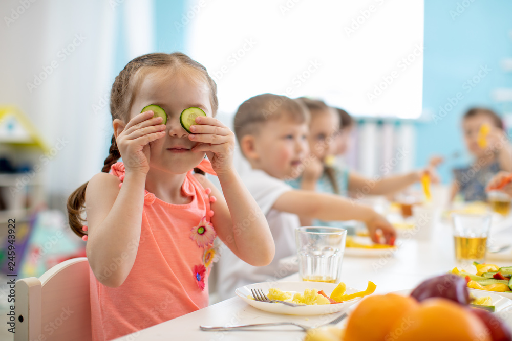 Fototapety, obrazy: Funny kid eating healthy food in kindergarten or daycare