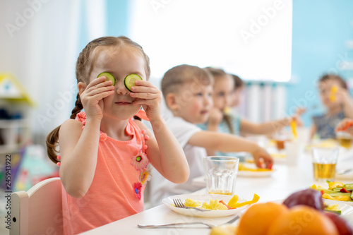 Funny kid eating healthy food in kindergarten or daycare