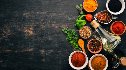 Zestaw przypraw i ziół. Kuchnia indyjska. Pieprz, sól, papryka, bazylia, kurkuma. Na czarnej drewnianej tablicy. Widok z góry. Wolna przestrzeń do kopiowania.