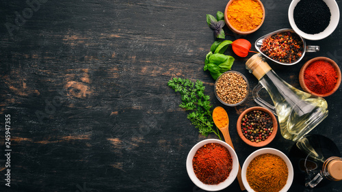 A set of spices and herbs. Indian cuisine. Pepper, salt, paprika, basil, turmeric. On a black wooden chalkboard. Top view. Free copy space.