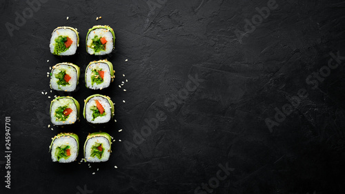 Poster de jardin Sushi bar Sushi roll with avocado, cucumber and tomato. Japanese cuisine. Top view. On a black background.