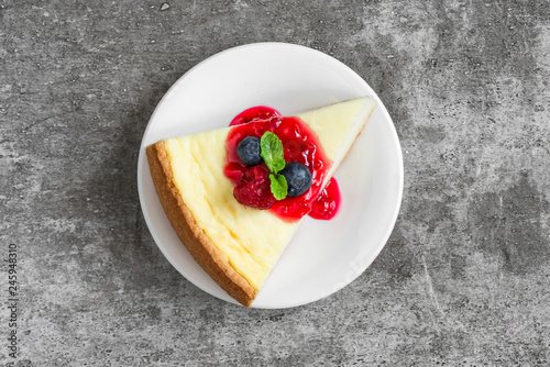 slice of cheesecake with fresh raspberries, blueberries, jam and mint on concrete background. top view