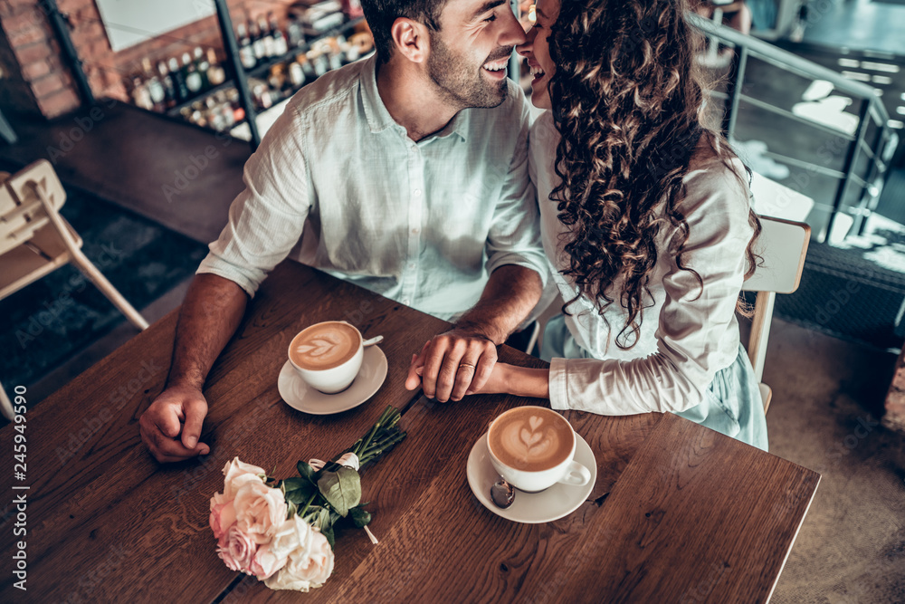 Fototapety, obrazy: Sincere feelings. A couple in love is enjoying each other sitting in a cafe and drinking coffee.