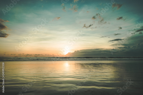 The sunset over the calm water surface. Picturesque twilight Asian landscape. The fall sun in the colorful sky over the ocean body. The peacefulness. Ideal place for the rest and relax.