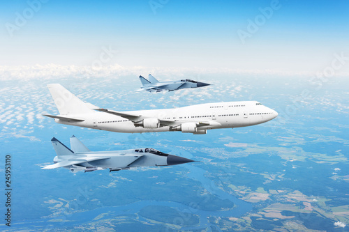 Large passenger plane, accompanied by two military fighter Fototapeta