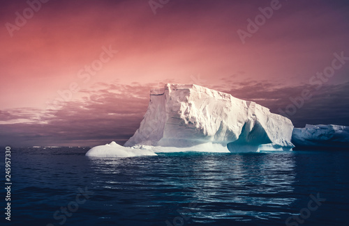 Deurstickers Antarctica The huge iceberg on the colorful sunset sky background. Breathtaking magic Antarctic landscape. The ice and snow covered glacier floating among the frozen polar ocean. Overwhelming fairy tale scene.
