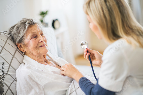 Canvastavla A health visitor examining a sick senior woman lying in bed at home with stethoscope