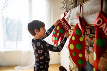 Boy Hanging A Christmas Stocking On A Fireplace