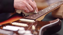 Man Cleans Electric Guitar Fretboard