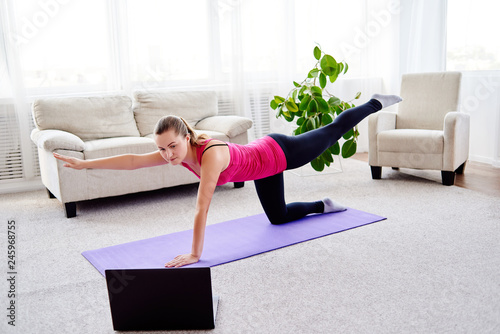 Fotografía  Beautiful young woman doing stretching exercise on floor at home, online training on laptop computer, copy space