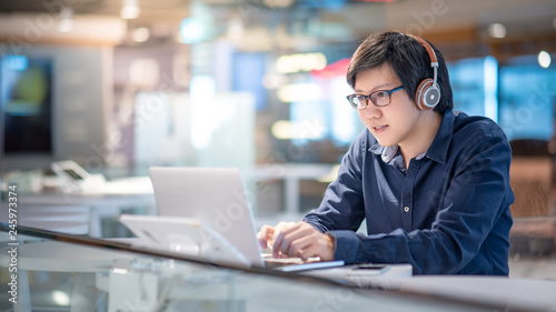 Asian business man listening to music by headphones while working with laptop computer in coworking space. Freelance or digital nomad lifestyle. Online shopping or E-commerce social media on internet