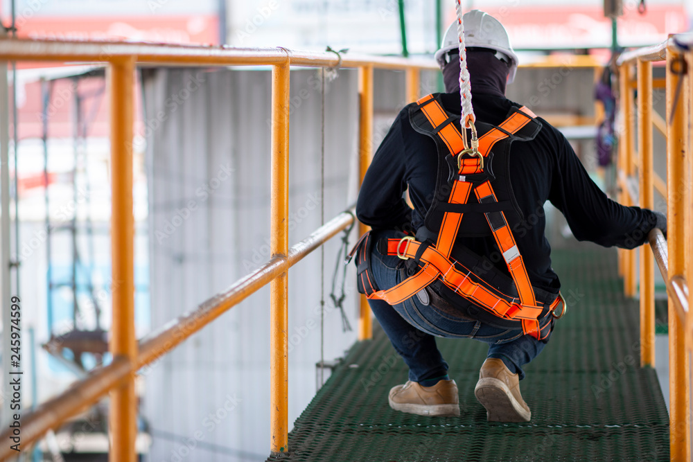 Fototapety, obrazy: Construction worker wearing safety harness and safety line working on construction.