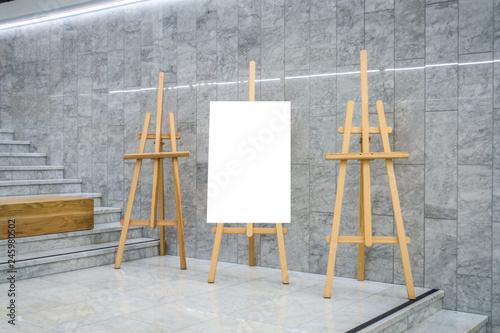 Photo Blank art board canvas and three wooden easels in exhibition gallery