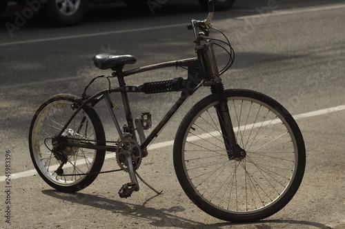 Fotobehang Fiets black bicycle on sunny street.