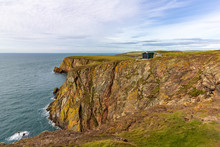 Building Perched On The Edge Of A Cliff Overlooking The Sea