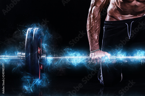 Foto auf Leinwand Akt Closeup photo of strong muscular bodybuilder athletic man pumping up muscles with barbell on black background. Workout energy bodybuilding concept. Copy space for sport nutrition ads.