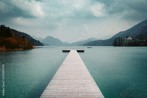 Wooden pier with clear lake in the Alps in summer
