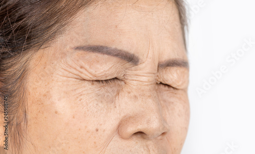 Obraz close up skin wrinkle and freckles of old asian woman face which closing eyes - fototapety do salonu