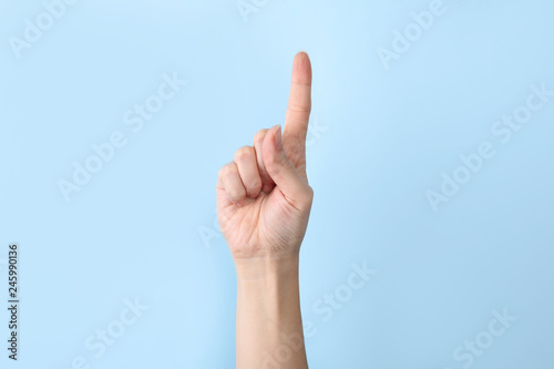 Woman showing number one on color background, closeup. Sign language
