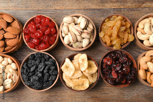 Composition of different dried fruits and nuts on wooden background, top view