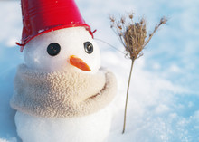 Little Snowman With A Bucket On The Head And In A Scarf On Snow In Sunny Winter Day