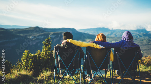 Poster Camping three friends sit in camping chairs on top of a mountain, travelers enjoy nature and cuddle, tourists look into distance on background of panoramic landscape, weekend concept mockup