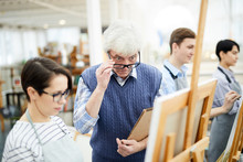 Portrait Of Mature Art Teacher Criticizing Work Of Student Painting Picture On Easel In Art Class, Copy Space