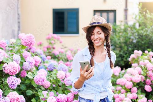 Happy woman is using mobile phone Fototapet