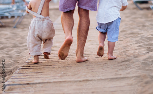 Photo A midsection of father with two toddler children walking on sand beach on holiday