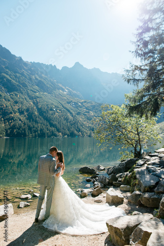 Slika na platnu Beautiful wedding couple standing on the stony shore of the lake Morski oko in the mountains