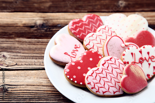 Obraz Valentine day heart shaped cookies in plate on brown wooden table - fototapety do salonu