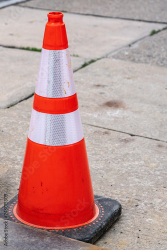 Fotografie, Obraz  bright orange and white reflective safety cone on the sidewalk with copy space